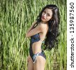 Portrait of beautiful woman with long dark hair wearing one-piece swimsuit - stock photo