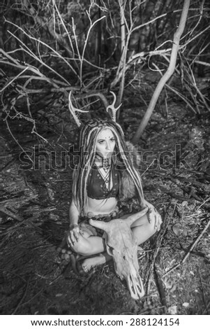 portrait of Beautiful woman with long dreadlocks hair sit near cow skull with horns against wild forest trees Young girl pray satan Woman shaman in ritual garment wear fur and leather clothes