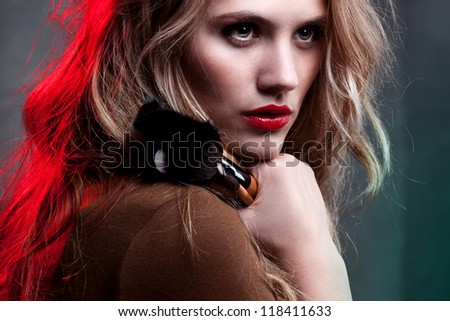 Portrait of beautiful woman with make up brushes on dark background