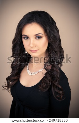 Portrait of beautiful woman with makeup and evening hairstyle in black dress - stock photo