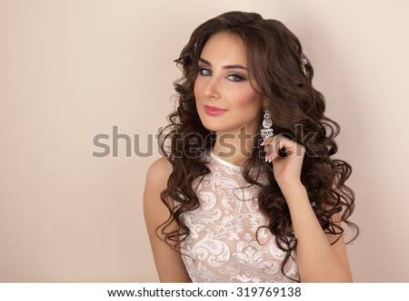 Portrait of beautiful woman with makeup and evening hairstyle in white dress - stock photo