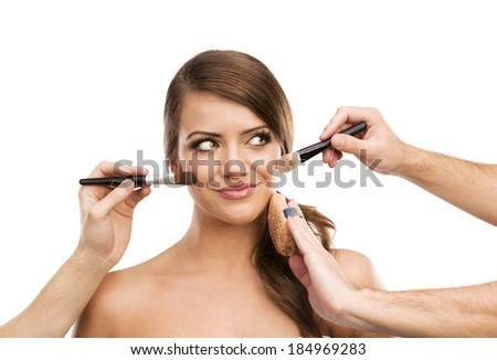 Portrait of beautiful woman with makeup brushes near attractive face, many hands applying make up on woman face isolated on white background