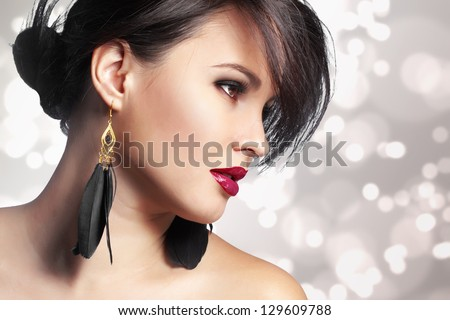 Portrait of beautiful woman with perfect make up over party lights - stock photo