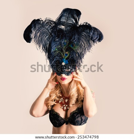Portrait of beautiful woman with purple feather mask against white background. Filtered image instagram style.