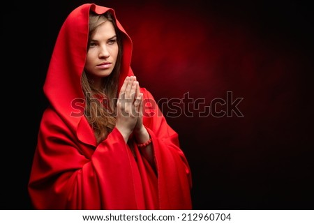 portrait of beautiful woman with red cloak  praying - stock photo