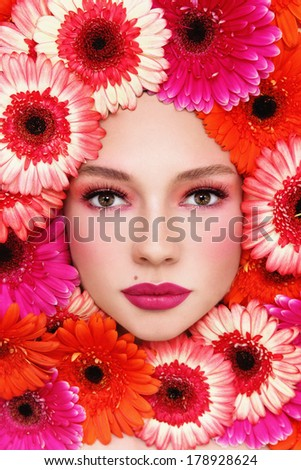 Portrait of beautiful woman with stylish make-up and bright flowers around her face
