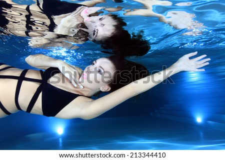 Portrait of beautiful woman with swimsuit underwater in the pool  - stock photo