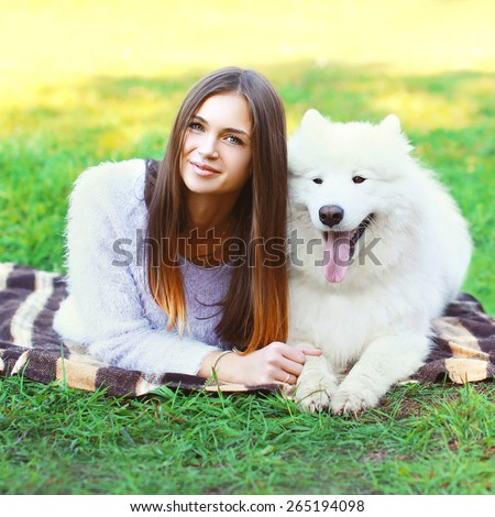 Portrait of beautiful woman with white Samoyed dog lying on the grass in sunny day - stock photo