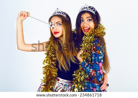 Portrait of beautiful women friends wearing bright sexy outfits, funny fake crowns  tinsel and magic want, ready for celebrating holidays party. having fun together screaming and making funny faces. - stock photo