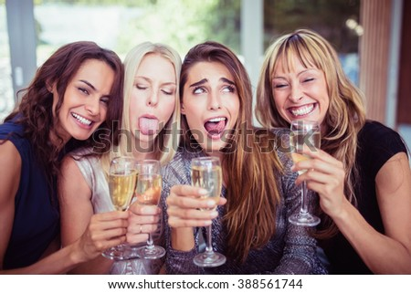 Portrait of beautiful women making funny faces and having drinks at party