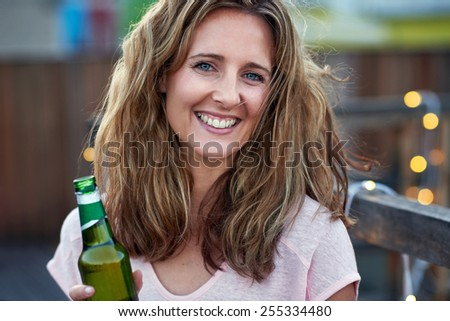 Portrait of beautiful women outdoors on rooftop with beer - stock photo