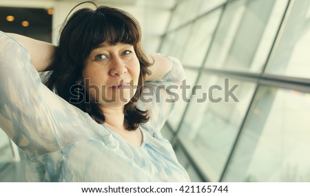 Portrait of beautiful 40 years old woman standing near the window - stock photo