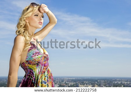 portrait of beautiful young adult blonde girl in sunglasses on background blue sky - stock photo