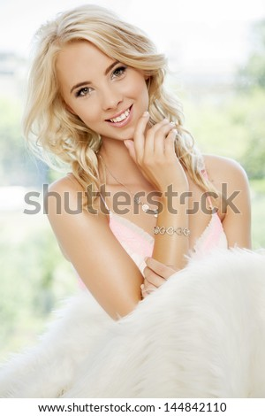 portrait of beautiful young adult sensuality blonde babe woman wrapped in white fur