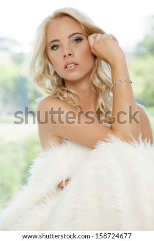 portrait of beautiful young adult sensuality romantic blonde woman wrapped in white fur