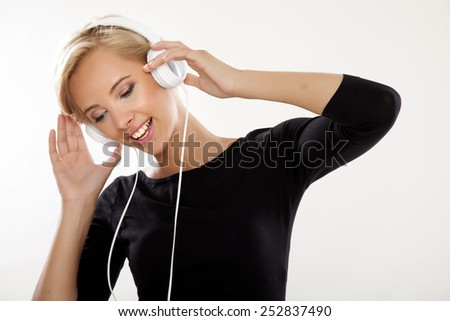 Portrait of beautiful young adult smiling sensuality sexy and attractive pretty blonde girl in black shirt is listen to the music in white headphones - stock photo