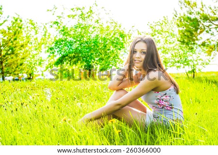 portrait of beautiful young adult woman sit on meadow against white flower on apple tree Cute slim girl in gray dress look at camera and enjoying against summer sky Empty Copy space for inscription - stock photo