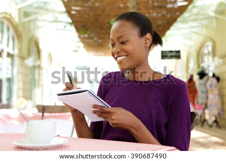 Portrait of beautiful young african american woman writing notes at cafe - stock photo