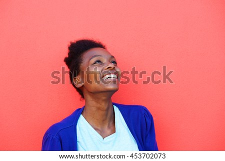 Portrait of beautiful young african female looking away and smiling against red background
