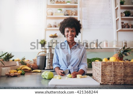 Portrait of beautiful young african woman standing behind the bar counter and chopping fresh fruits. Woman working at juice bar. - stock photo