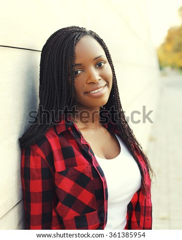 Portrait of beautiful young african woman with dreadlocks hair in city - stock photo