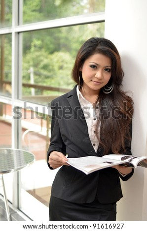 Portrait of beautiful young Asian  business woman reading a magazine