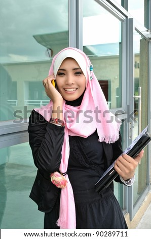 Portrait of beautiful young Asian Muslim business woman talking on the mobile phone while holding a laptop - stock photo