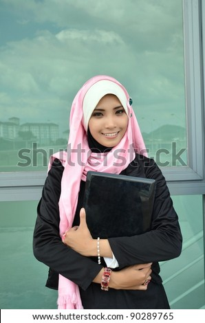 Portrait of beautiful young Asian Muslim business woman with holding a laptop
