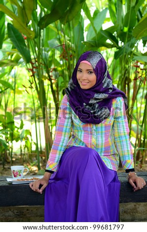 Portrait of beautiful young Asian Muslim student smile outdoors