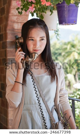 portrait of beautiful young asian woman  talking on vintage telephone - stock photo