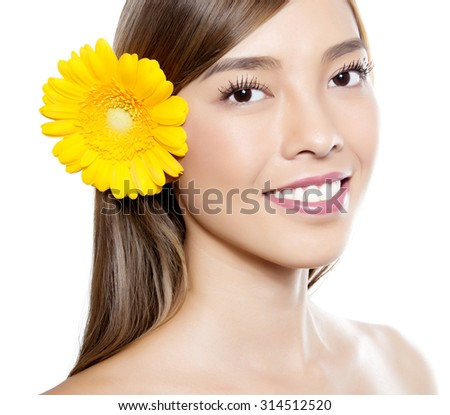 portrait of beautiful young asian woman with clear skin isolated on white with yellow flower