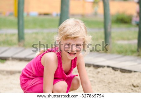 portrait of beautiful young blond girl laughing in the playground - stock photo