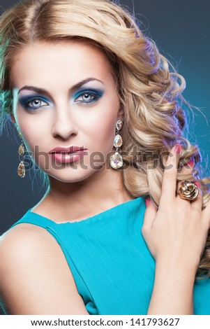 Portrait of beautiful young blond girl with bright glamorous make-up and curly hair
