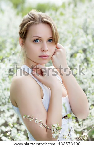 Portrait  of beautiful young blond woman in blooming garden - stock photo