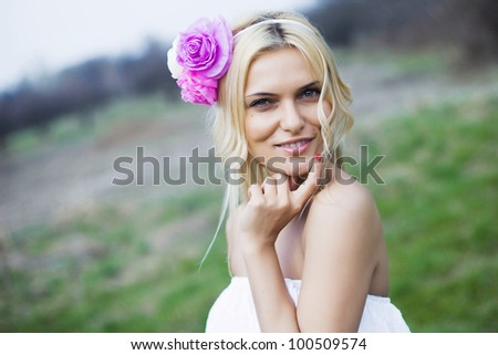 Portrait of beautiful young blond woman in white blouse at park holding her lips - stock photo
