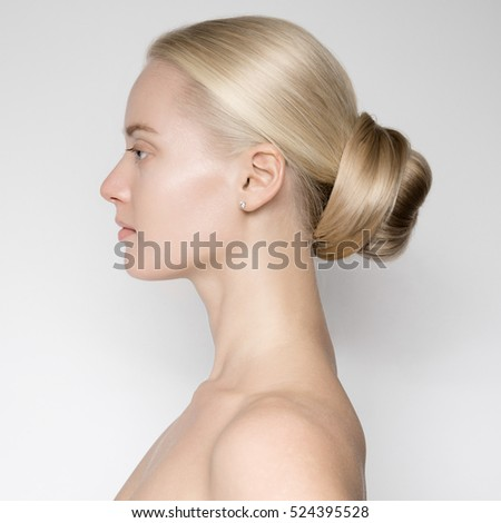 Portrait Of Beautiful Young Blond Woman With Bun Hairsty?le. Side View
