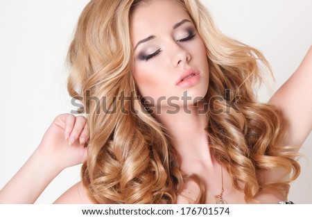 Portrait of beautiful young blond woman with clean face and curly hair, spa woman with perfect skin and daily makeup. Beautiful woman face closeup. Studio isolated - stock photo