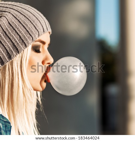 Portrait of beautiful young blonde teenage girl in beanie hat blows big bubble from bubble gum - stock photo