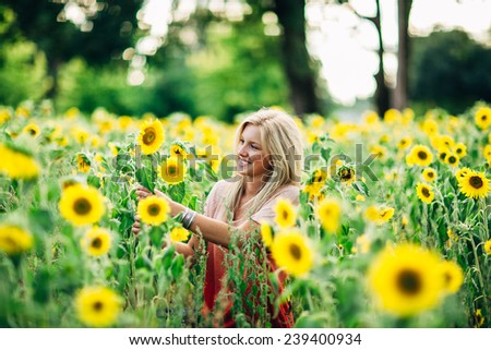portrait of beautiful young blonde woman grabbing sunflower and smiling again - stock photo