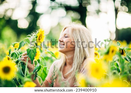 portrait of beautiful young blonde woman grabbing sunflower smiling at sunflower - stock photo