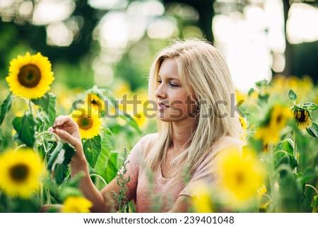portrait of beautiful young blonde woman grabbing sunflower staring - stock photo