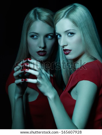 portrait of beautiful young blonde woman in teal lighting touching her reflection in mirror with fingers - stock photo