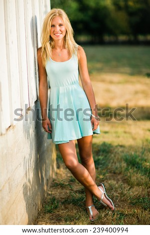 portrait of beautiful young blonde woman leaning against white wall outside smiling - stock photo
