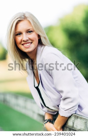 portrait of beautiful young blonde woman leaning over fence smiling - stock photo