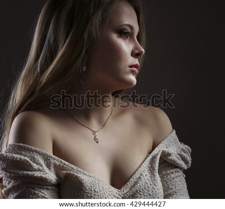 Portrait of beautiful young blonde woman on black background
