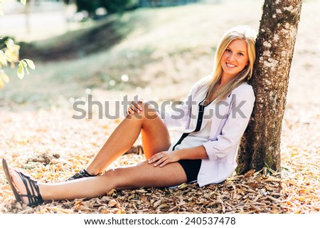 portrait of beautiful young blonde woman outside sitting by tree - stock photo
