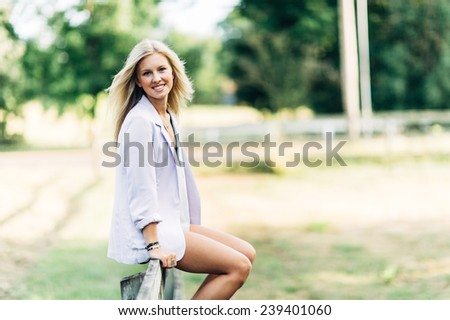 portrait of beautiful young blonde woman sitting on fence smiling - stock photo