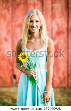 portrait of beautiful young blonde woman standing in front of red wall holding sunflower smiling - stock photo