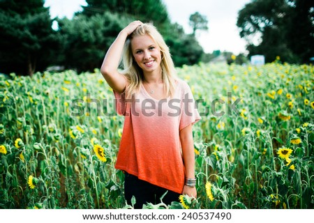 portrait of beautiful young blonde woman standing in front of sunflowers hand on hair - stock photo