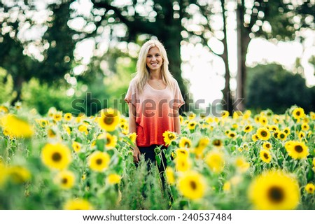portrait of beautiful young blonde woman standing in front of sunflowers smiling - stock photo